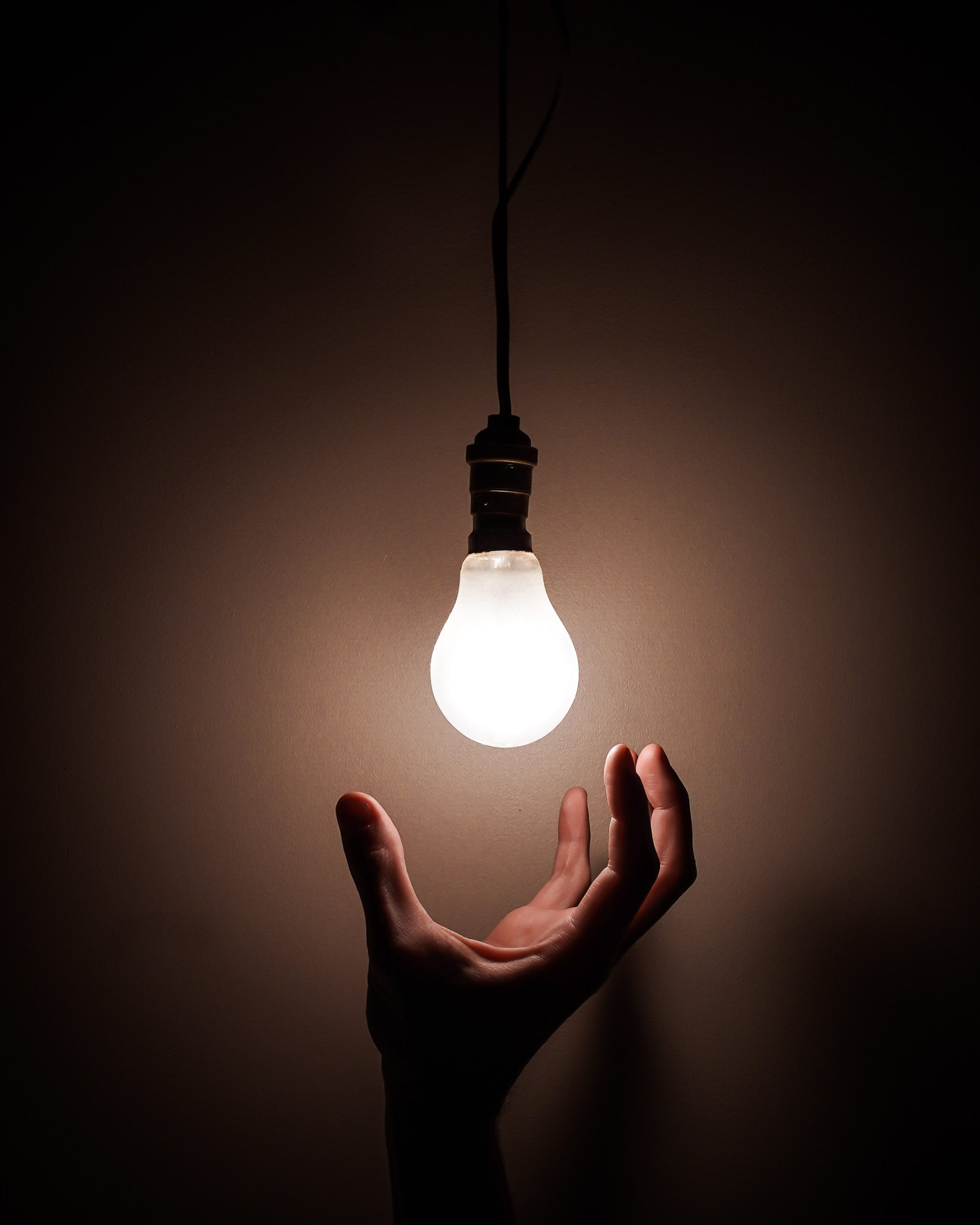 person holding white light bulb 3651820 scaled